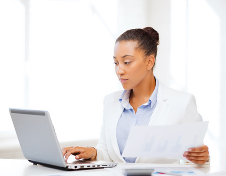 computer learning: business and tax concept - african businesswoman working with computer in office