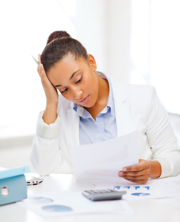business dilemma: business and tax concept - african businesswoman working with calculator in office