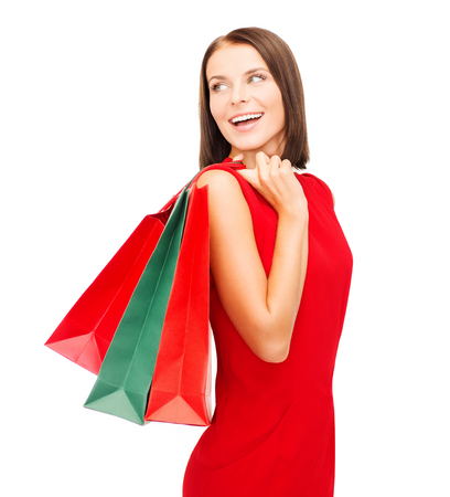 christmas shopping: shopping, sale, gifts, christmas, x-mas concept - smiling woman in red dress with shopping bags