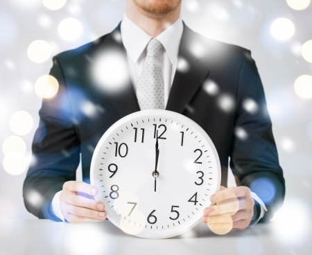 12 hour: holiday, celebration, new years eve concept - man holding wall clock showing 12 Stock Photo