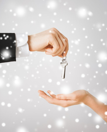 property, ownership, home, real estate concept - man hand passing house keys to woman Stock Photo - 22642117