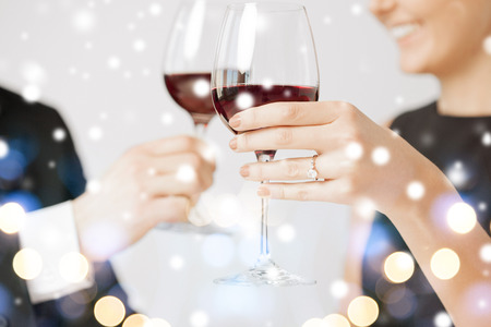 love, romance, holiday, celebration concept - engaged couple with wine glasses in restaurant photo