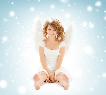 holidays and costumes concept - happy teenage angel girl photo