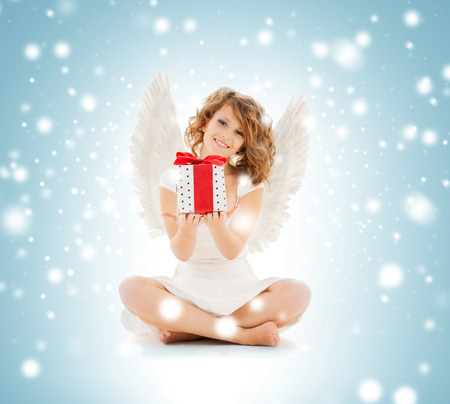 holidays, xmas and costumes concept - happy teenage angel girl with christmas gift photo
