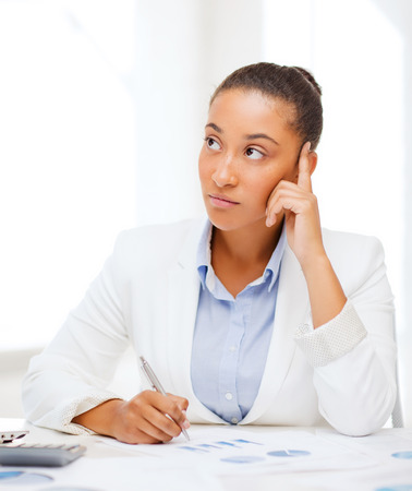analytical: business and tax concept - african businesswoman working with calculator in office