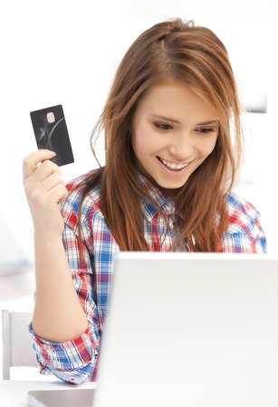 online and internet shopping concept - happy teenage girl with laptop and credit card Stock Photo - 22642166