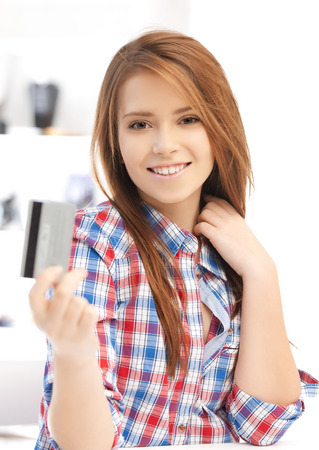 banking and shopping concept - happy teenage girl with credit card photo