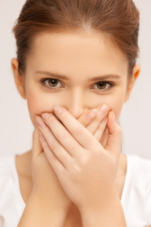 hands covering face: speak no evil concept - face of beautiful teenage girl covering her mouth