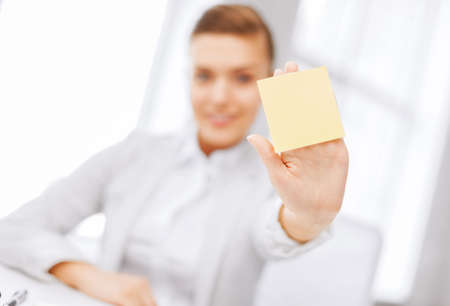 business, office, school and education concept - smiling businesswoman showing blank sticky note photo
