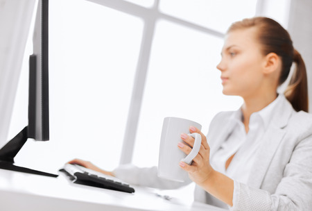 business, office, school and education concept - businesswoman with computer in office drinking coffee