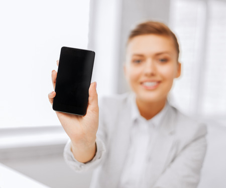 business, office, school and education concept - smiling businesswoman with smartphone in office photo