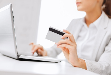 bankieren, winkelen, geld concept - zakenvrouw met laptop en creditcard Stockfoto