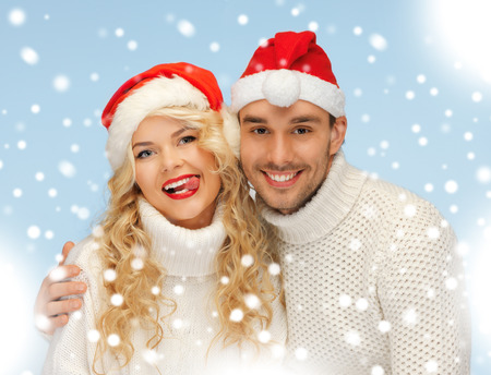 christmas, x-mas, winter, happiness concept - family couple in sweaters and santa's hats photo