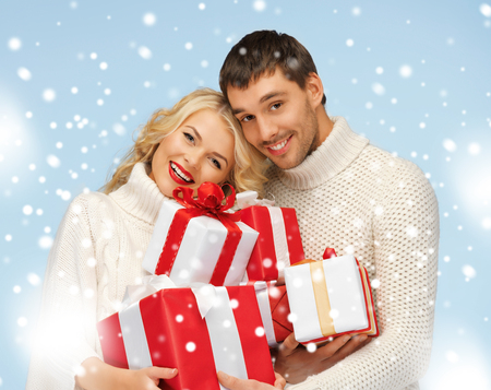 christmas, x-mas, winter, happiness concept - happy man and woman with many gift boxes photo
