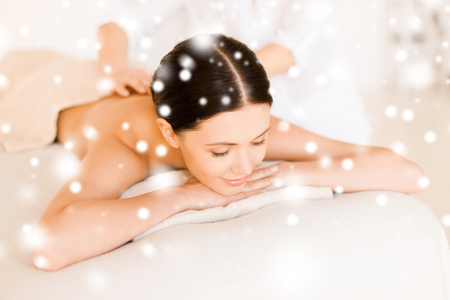 therapeutic massage: health and beauty concept - woman in spa salon getting massage Stock Photo