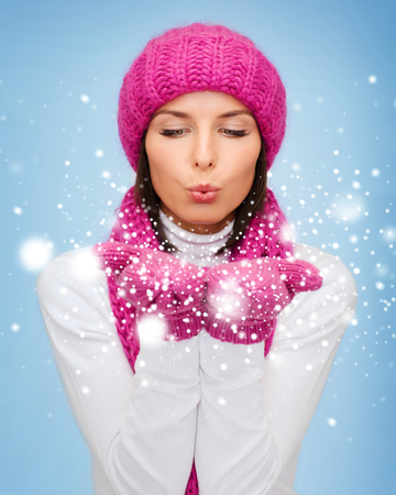 christmas, x-mas, people, happiness concept - happy woman in winter clothes blowing on palms photo