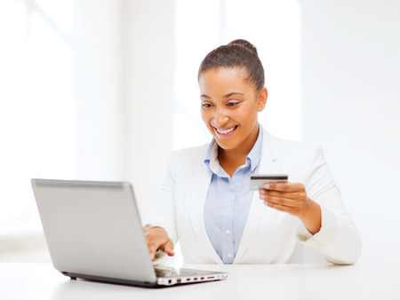 woman buying: business, banking, technology, money, shopping concept - smiling businesswoman with laptop and credit card