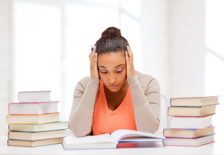education and business concept - tired student with pile of books and notes studying indoors photo