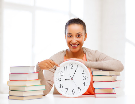 business, office, school and education concept - attractive woman showing clock photo