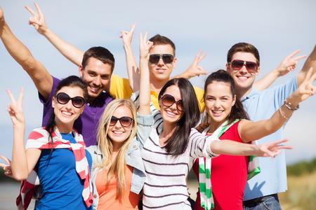 personas saludandose: verano, vacaciones, vacaciones, concepto de la gente feliz - grupo de amigos que se divierten en la playa