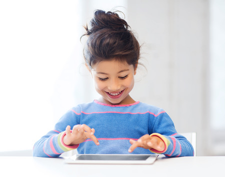 education, school, technology and internet concept - little student girl with tablet pc at home