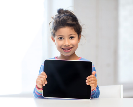 education, school, technology and internet concept - little student girl with tablet pc at home photo