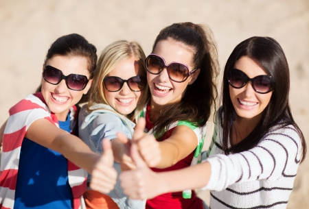 females: summer, holidays, vacation, happy people concept - beautiful teenage girls or young women showing thumbs up