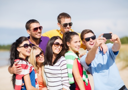 group picture: summer, holidays, vacation, happy people concept - group of friends taking picture with smartphone
