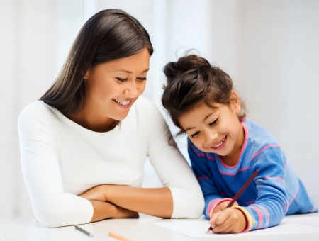 elementary kids: family, children and happy people concept - mother and daughter drawing Stock Photo