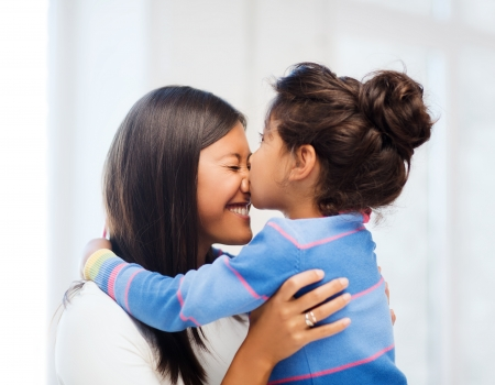 children playing together: family, children and happy people concept - hugging mother and daughter Stock Photo