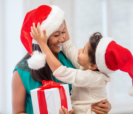 holidays, presents, christmas, x-mas concept - happy mother and child girl in santa helper hats with gift box photo