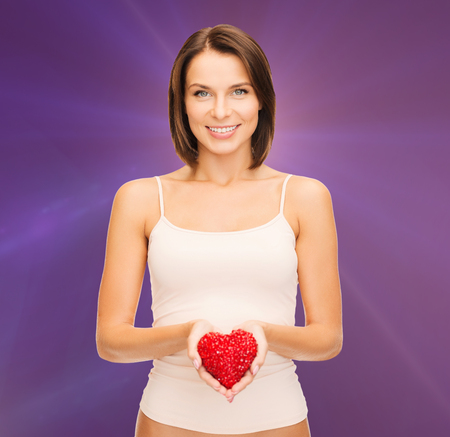 health, charity and beauty concept - beautiful woman in cotton underwear showing red heart photo