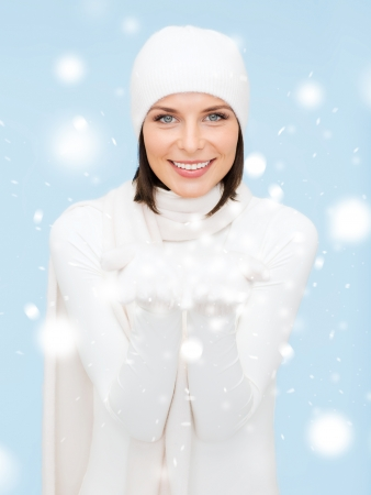 seasonal, people, happiness concept - smiling woman in winter clothes with something on palms photo