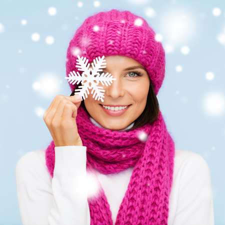 pink hat: winter, people, happiness concept - woman in hat and muffler with big snowflake