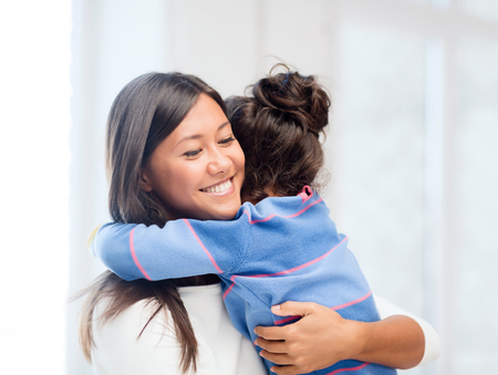 family, children and happy people concept - hugging mother and daughter photo