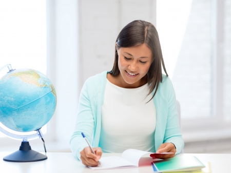 education and school, travel concept - female teacher with globe and notepad photo