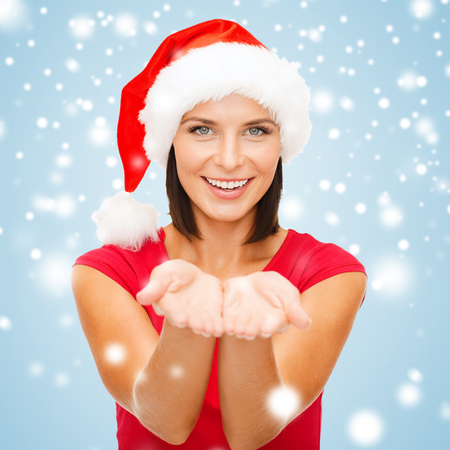 christmas, x-mas, winter, happiness concept - smiling woman in santa helper hat with something on palms photo