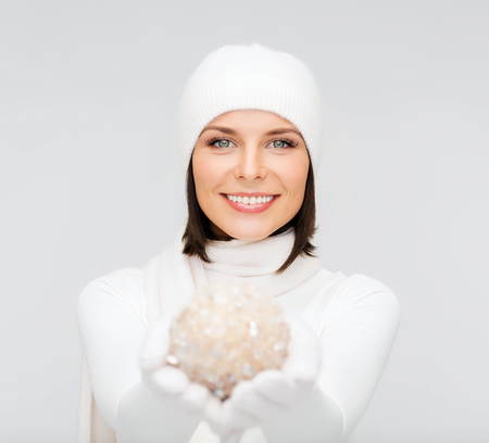 winter, people, happiness concept - woman in hat, muffler and gloves with christmas decoration ball photo