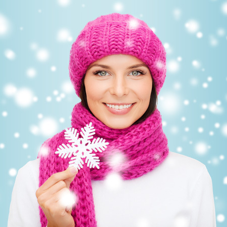 winter, people, happiness concept - woman in hat and muffler with big snowflake photo