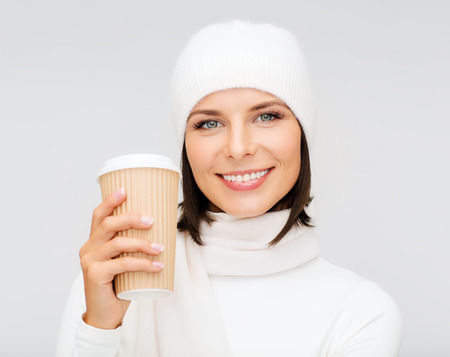 take away: winter, people, happiness, drink and fast food concept - woman in hat with takeaway tea or coffee cup Stock Photo
