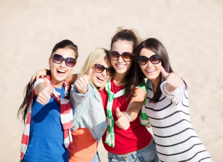 women having fun: summer, holidays, vacation, happy people concept - beautiful teenage girls or young women showing thumbs up