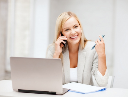 social worker: business and communication - smiling businesswoman with smartphone in office Stock Photo