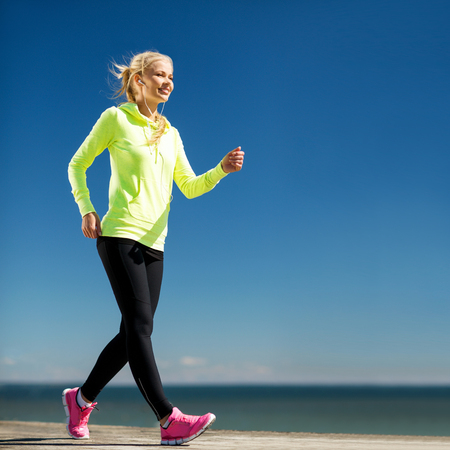 earbud: fitness and lifestyle concept - woman doing sports outdoors