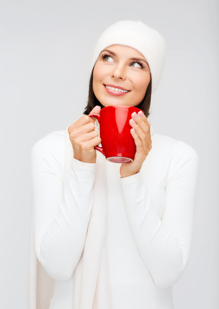 winter, people, happiness, drink and food concept - woman in hat with red tea or coffee mug photo