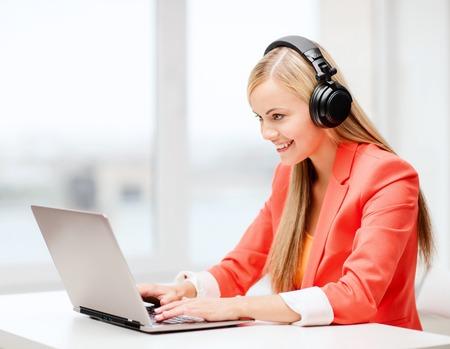 레저, 음악, 자유 시간, 온라인 및 인터넷 개념 - 헤드폰은 음악을 듣고 행복 한 여자 스톡 콘텐츠