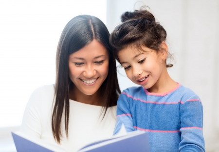 family, children, education, school and happy people concept - mother and daughter with book photo