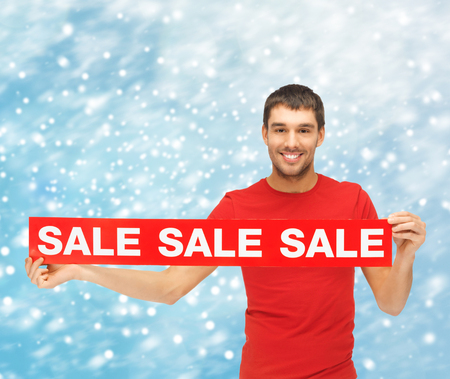 shopping, gifts, christmas, x-mas concept - smiling man in red shirt with sale sign photo