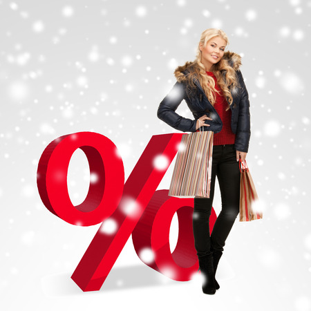 sale, christmas, x-mas and holidays concept - woman with shopping bags and big red percent sign photo