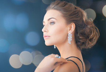 earring: jewelry, luxury, vip, nightlife, party concept - beautiful woman in evening dress wearing diamond earrings