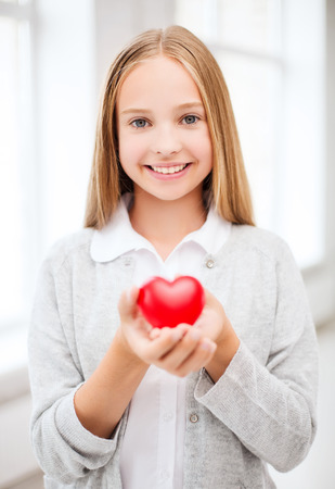 health, charity and beauty concept - beautiful teenage girl showing red heart photo